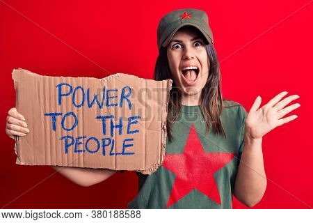 Beautiful woman wearing t-shirt with red star communist symbol asking for social movement celebrating achievement with happy smile and winner expression with raised hand