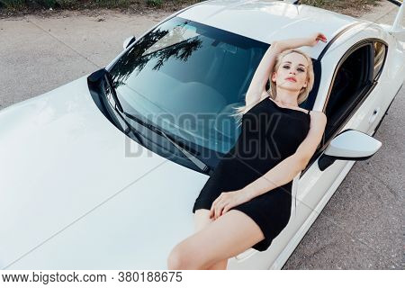 Beautiful Blonde In A Black Dress Lies On The Bonnet Of A Car