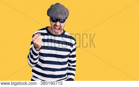 Middle age handsome man wearing burglar mask angry and mad raising fist frustrated and furious while shouting with anger. rage and aggressive concept.