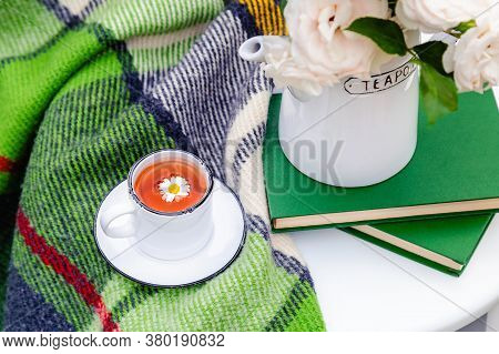 Cup Of Chamomile Herbal Tea With Chamomile Flower And Teapot, Books, Warm Plaid On White Table Outdo