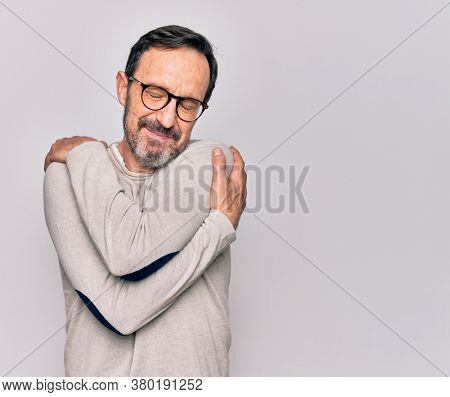 Middle age handsome man wearing casual sweater and glasses over isolated white background hugging oneself happy and positive, smiling confident. Self love and self care