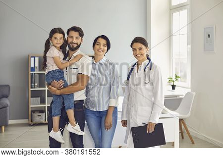 Family At A Doctors Consultation At The Clinic. Parents With Child And Woman Therapist Are Smiling W