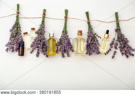 Lavender Oil Serum With Fresh Lavender Flower Bouquets Are Drying On White Wooden Background. Lavend