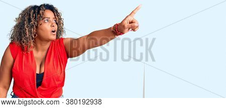 Young african american plus size woman wearing casual style with sleeveless shirt pointing with finger surprised ahead, open mouth amazed expression, something on the front