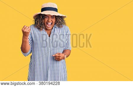 Young african american plus size woman wearing summer hat angry and mad raising fist frustrated and furious while shouting with anger. rage and aggressive concept.