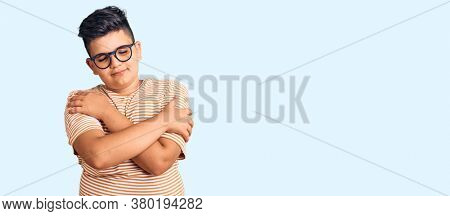 Little boy kid wearing casual clothes and glasses hugging oneself happy and positive, smiling confident. self love and self care