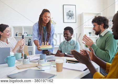 Multi-ethnic Group Of People Celebrating Birthday In Office, Focus On Smiling Woman Bringing Cake To