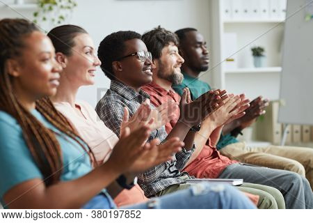 Side View Portrait Of Multi-ethnic Group Of People Applauding While Sitting In Row In Audience Or Co