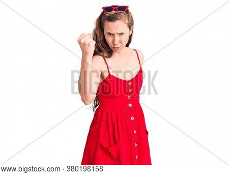 Young beautiful blonde woman wearing casual dress angry and mad raising fist frustrated and furious while shouting with anger. rage and aggressive concept.