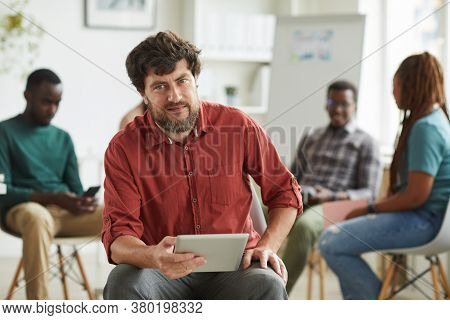 Multi-ethnic Group Of People Sitting In Circle While Discussing Business Project In Office, Focus On