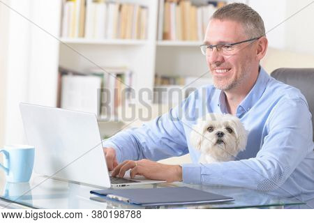 Man working at home and holding his liitle dog.
