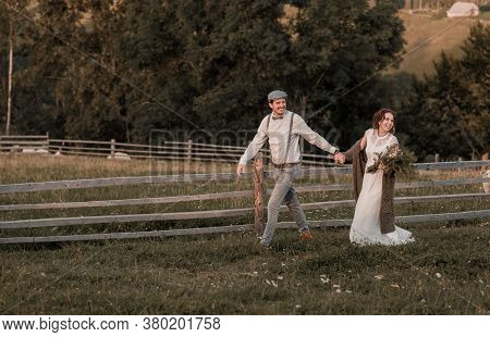 Young Wedding Romantic Couple Of Bride In White Dress And Bridegroom In Suit On Pasture Of Sheeps. W