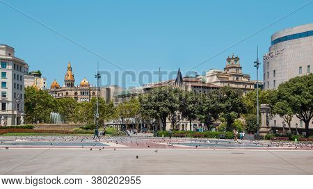 BARCELONA, SPAIN - AUGUST 7, 2020: Few people walking by the popular Catalunya Square in Barcelona, during the pandemic Covid-19 situation, when usually is the busiest square in the center of city