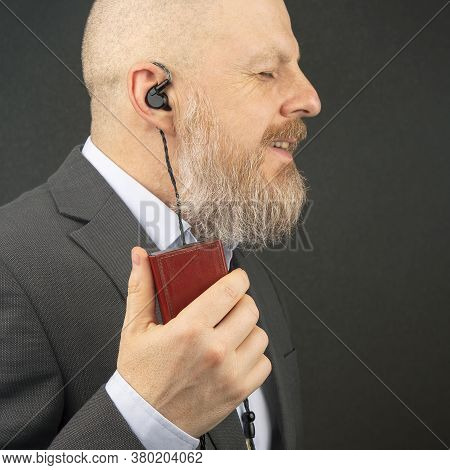 Bearded Business Man Enjoys Listening To His Favorite Music From An Audio Player With Small Headphon