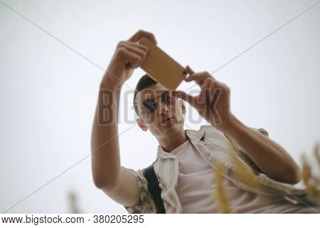 Photo Of A Man From Below Taking A Photo Of The Field On His Smartphone