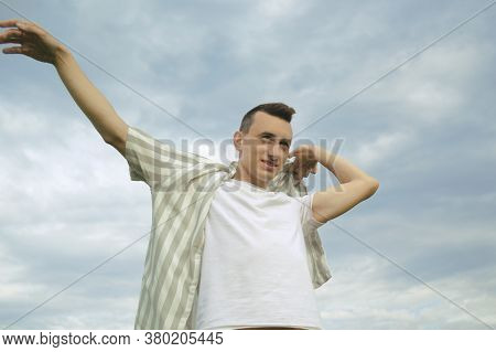 Handsome Guy Puts On A Shirt Against The Background Of The Sky. Men's Fashion, Unity With Nature.