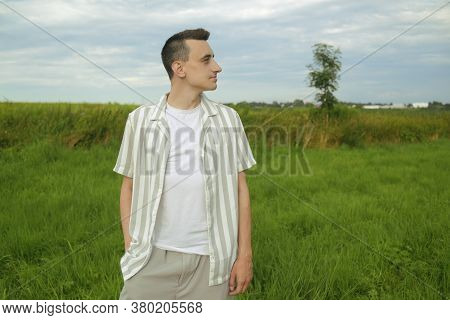 A Fashionably Dressed Guy Walking In A Field Outside The City. Man Breathes Fresh Air, Unity With Na