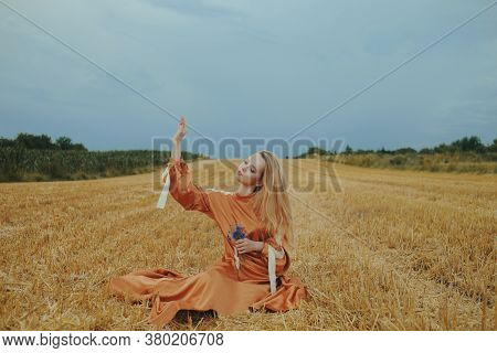 A Beautiful Girl In A Dress Sits On A Wheat Field. Fabulous Photo Of A Blonde Outside The City. A Wo