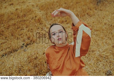 A Gorgeous Girl In A Long Dress Sits On A Wheat Field. Blonde Posing For A Fashionable Photo. Woman