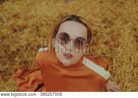 A Gorgeous Girl In A Long Dress Sits On A Wheat Field. Blonde Posing For A Fashionable Photo. Portra