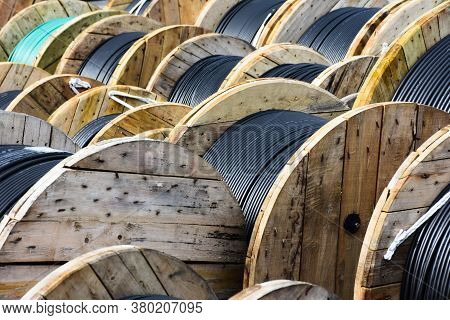 Wooden Coils Of Electric Cable Outdoor. High And Low Voltage Cables In The Storage.