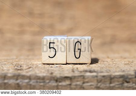 Technology Name 5G On A Wooden Cube On Wooden Background, Mobile Or Technology Concept