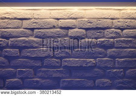 Brick Wall Indigo Lighting. White Wall Blue Glow In Modern Vintage Loft Interior. Unusual Room Desig
