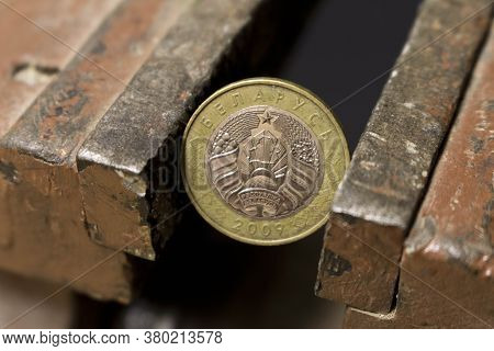 A Coin In A Metal Vise. Concept Of Economic Problems. Selective Focus. Close Up