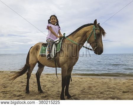Portrait Asian Child Girl Riding Horse On A Beach Of Thailand In Evening, Background Of Sea And Sky.