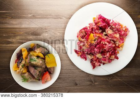 Herring Under A Fur Coat On A White Plate. Herring Under A Fur Coat On A Brown Wooden Background. He