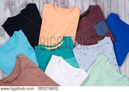 Many Colorful T-shirts On The Wooden Background. Top View, Flat Lay. T-shirts Folded. Different T-sh