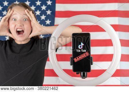 A Teenager Holds A Smartphone With The Tiktok Logo And The Word Banned And The American Flag In His