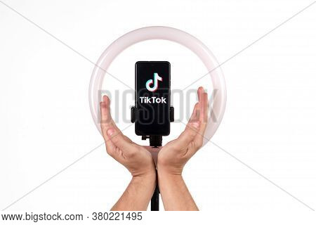 The Tiktok Logo On A Smartphone Attached To A Round Lamp With A Tripod And Male Hands Show Protectio