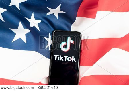 Close-up Tiktok Application Logo On A Smartphone With American Flag Background. Donald Trump To Ban