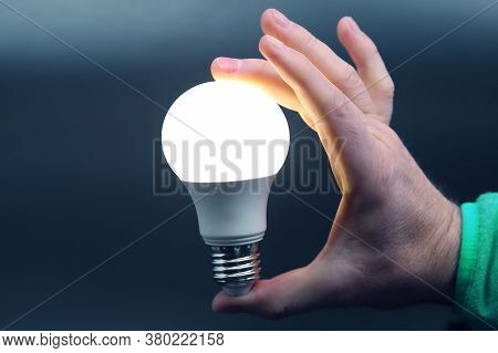 Human Hand Holding The Included Led Lamp On A Dark Background. Electricity And Led Industry