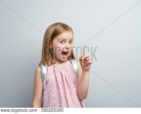 Little girl with school backpack pointing finger up, idea concept