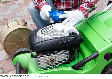 A Man Checking The Fuel Level In Lawn Mower. A Green Lawnmower. Gardening. Maintenance Of Equipment.