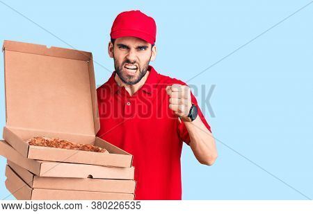 Young handsome man with beard wearing delivery uniform holding boxes with pizza annoyed and frustrated shouting with anger, yelling crazy with anger and hand raised