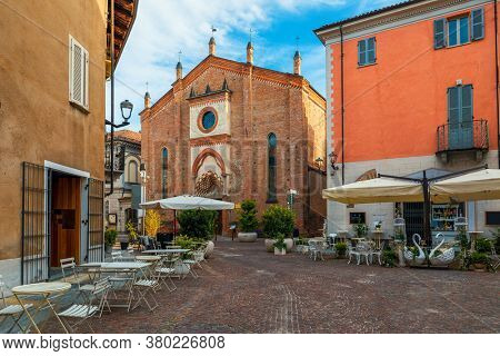 Narrow cobblestone street among old houses and San Domenico church in town of Alba in Piedmont, Northern Italy.