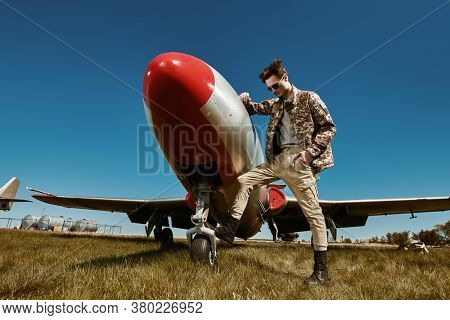 Handsome man pilot wearing military uniform stands by his fighter jet at the airfield. Military aircraft.