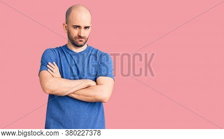 Young handsome man wearing casual t shirt skeptic and nervous, disapproving expression on face with crossed arms. negative person.