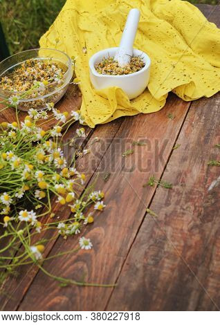 Organic chamomile flowers in porcelain pestle standing on a wooden table, nature treatment concept