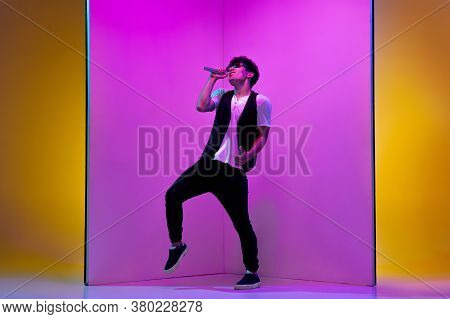 Inspired. Young Male Musician, Singer Performing On Pink-orange Background In Neon Light. Concept Of