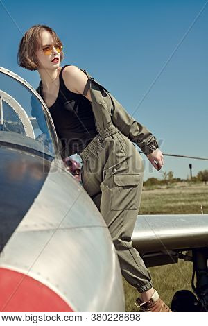 Portrait of a beautiful girl pilot sits in her fighter airplane at the airfield.