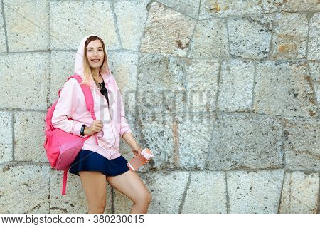 Young Athletic Woman With Backpack And Sports Mat Doing Sport Outside In Bright Sports Suit.