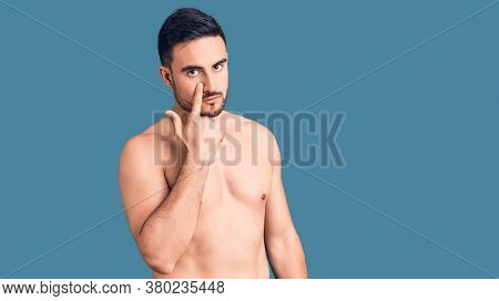 Young handsome man wearing swimwear pointing to the eye watching you gesture, suspicious expression