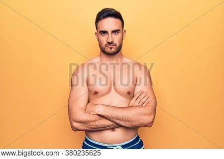 Young handsome man with beard wearing sleeveless t-shirt standing over yellow background skeptic and nervous, disapproving expression on face with crossed arms. Negative person.