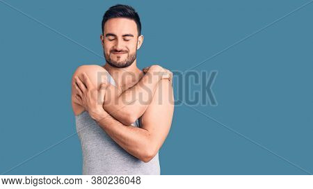 Young handsome man wearing swimwear and sleeveless t-shirt hugging oneself happy and positive, smiling confident. self love and self care