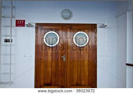 Traditional Teak doors with circular windows on Promenade deck leading to internal atrium and lobby on luxury cruise liner
