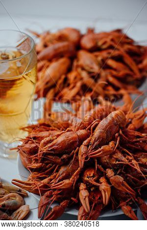 Two Large White Plates With Boiled Crawfish, Boiled Shrimps And Glass Of Beer On A Light Background